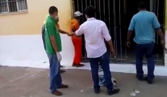 Diretor de Pedrinhas recebendo o celular na mão do preso